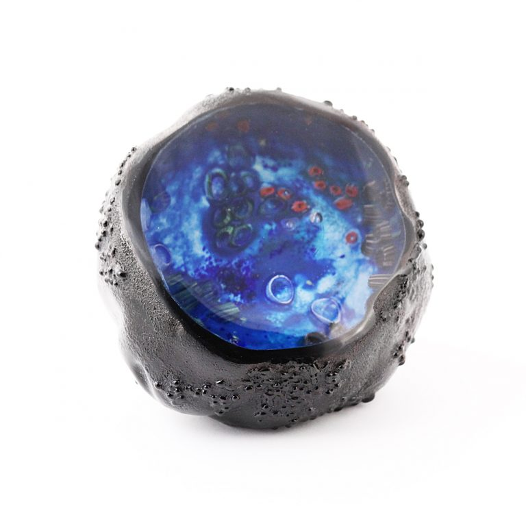 A Glass paperweight called an Inscape which shows an interior realm within a stone that is cut open. This one is made entirely from molten glass in our studios.