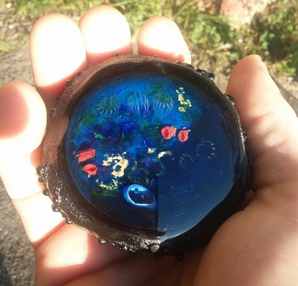 Parker holds a small blue Inscape Geode with a black shell in his hand for scale.