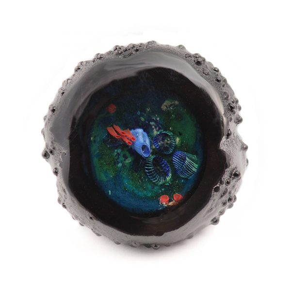 A glass geode with an inner world inside. In a variety of colors, this piece is blue and green to create an aquatic feeling. The piee is surrounded on the outside with a black rocky textural surface that shrouds all views except from the front. the front opening is ground smooth and highly polished to see to the interior. A visitor from another world that fits in your hand. This size is two and a half inches to three and a half inches in diameter. Made in the U.S.A.